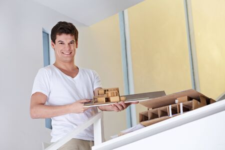 Happy architectural student showing building draft made of wood and cardboard photo