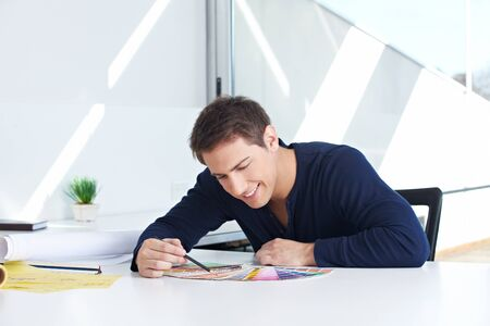 Graphic designer sitting with color fans and pencil in his office Stock Photo - 15542555