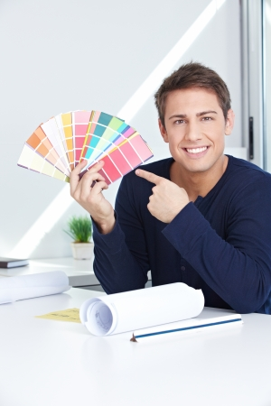 Happy graphic artist in his office showing color fan photo