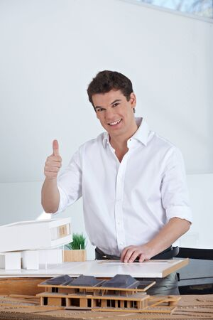 architectural firm: Happy architect with house model in his office holding his thumbs up Stock Photo