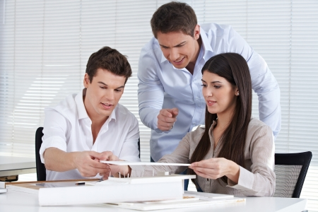 Three architects in an office creating a house model together Stock Photo - 15460595
