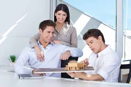 Architect showing house model to smiling couple in his office photo