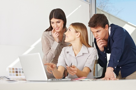 style advice: Creative business team working togetger at laptop in office