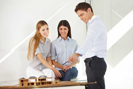 Architect with trainees in office explaining a building model Stock Photo - 15529975