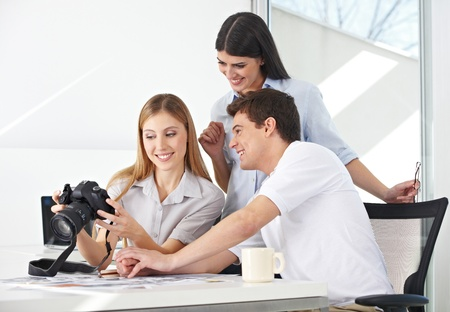 Female photographer viewing images on camera with her team in the office photo
