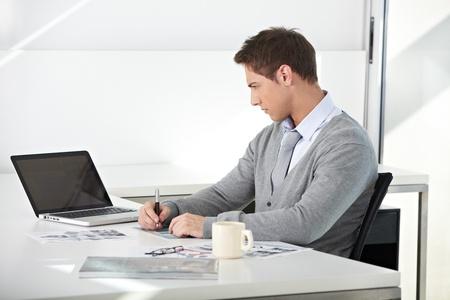 administracion de empresas: Estudiante creativo que trabaja con su computadora portátil en el escritorio