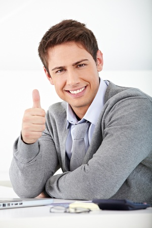 self confidence: Happy smiling business man holding his thumbs up