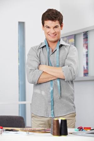 Smiling fashion designer in the studio with tape measure around his neck Stock Photo - 15530004