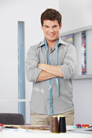 cross arms: Smiling fashion designer in the studio with tape measure around his neck Stock Photo