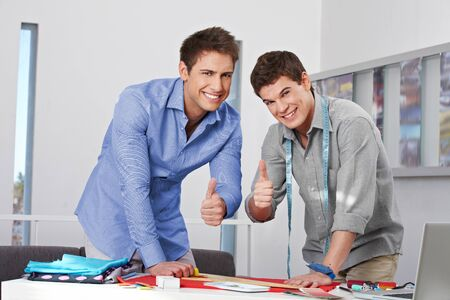 Two happy Fashion designer in their studio holding the thumbs up photo