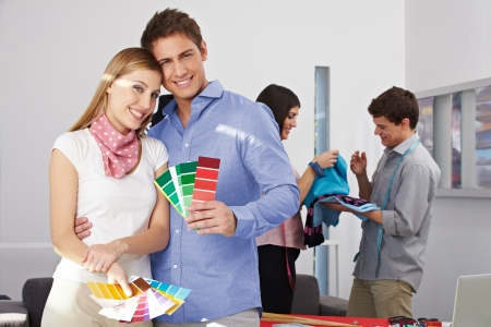 alteration shop: Two happy fashion designer holding color fan samples in their studio Stock Photo