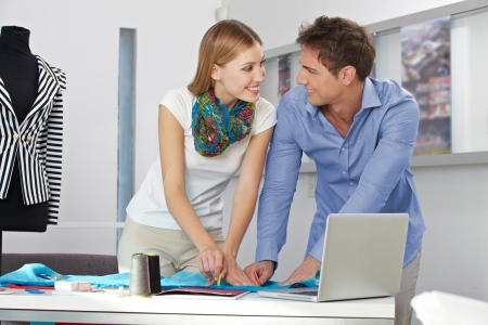 Two smiling fashion designer working together in their studio Stock Photo - 15574698