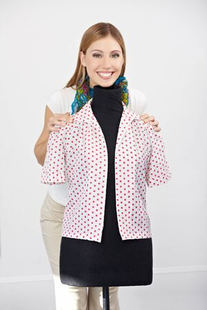 alteration shop: Happy smiling woman standing behind a dress form with blouse