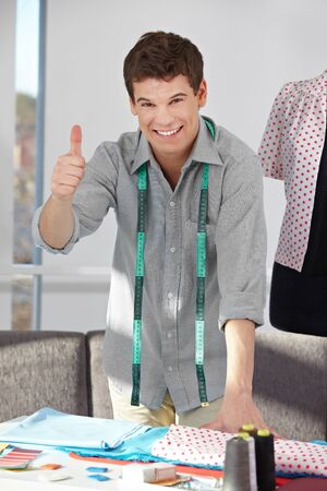 textile industry: Happy fashion designer holding thumbs up in his studio Stock Photo