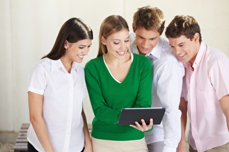 fun at work: Group of happy students looking at a tablet computer