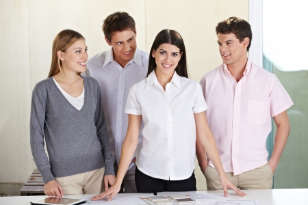 Happy team group in architectural office behind desk Stock Photo - 15529997