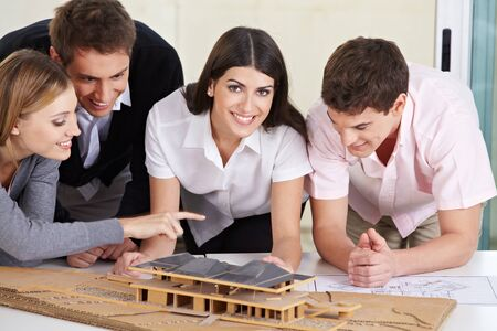 architectural studies: Four architects discussing a 3D house draft in their office