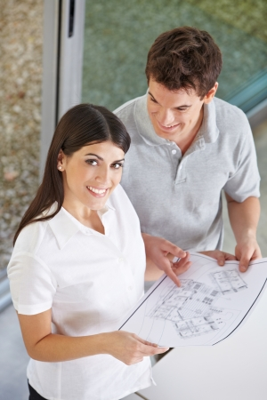 architectural firm: Happy attractive couple holding architectural drawing in their hands Stock Photo
