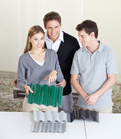 architectural firm: Happy couple at roofer looking at different corrugated panels for new roof