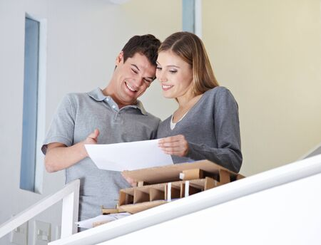 architectural firm: Two happy architectural students talking about a building plan Stock Photo