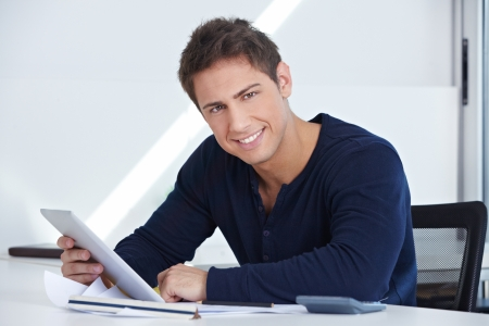 Happy designer sitting at his desk with a tablet computer in his hand Stock Photo - 15529985