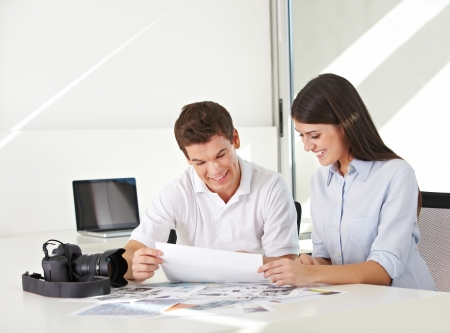Picture desk in stock photo agency with images and camera on their desk photo