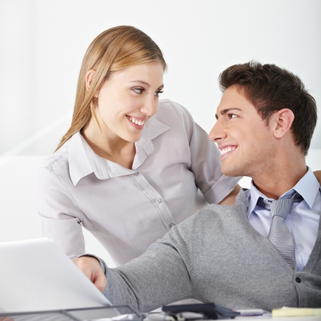 Smiling young business woman flirting with a man in the office photo