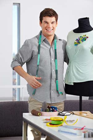 Happy fashion designer standing with dress form in his studio Stock Photo - 15611778