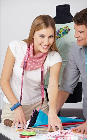 Female happy fashion designer working with assistant in her studio Stock Photo - 15611745