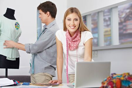 Two fashion designer working in studio with laptop computer and dress form Stock Photo - 15611721