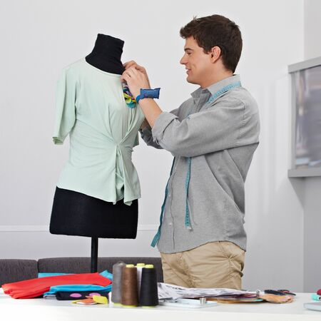 Man working as tailor on a dress form in his studio Stock Photo - 15611773