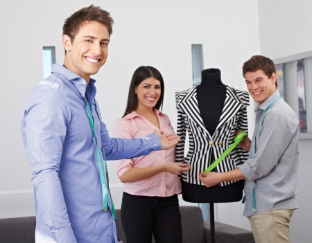 Happy fashion design students showing collection on a dress form Stock Photo - 15638054