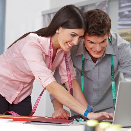 Two happy fashion designer browing the internet with a laptop computer Stock Photo - 15611772