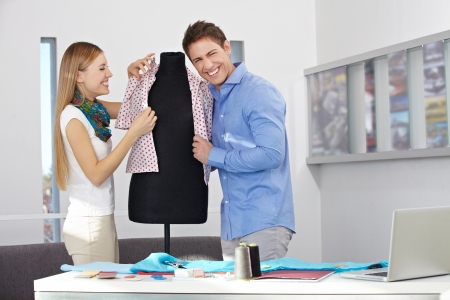 alteration shop: Happy man and woman in a studio dressing a dress form
