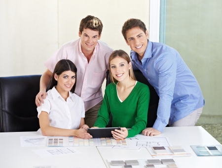 architectural firm: Smiling happy team of architects with tablet computer at desk Stock Photo