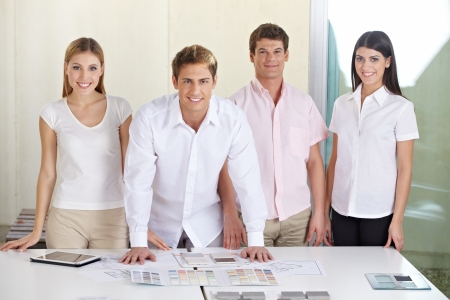 Happy team in architecture office standing behind desk Stock Photo - 15611692
