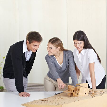 architectural studies: Three architecture students discussing 3D building model on desk