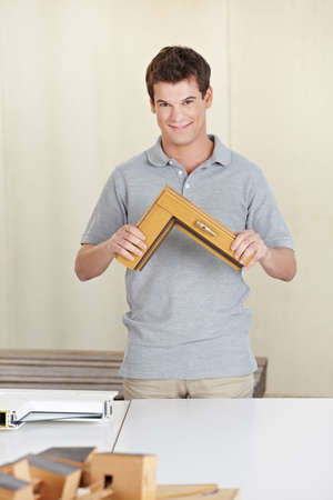 architectural firm: Happy carpenter holding a window frame sample in his work shop Stock Photo