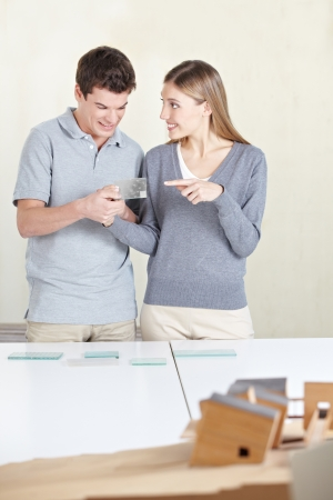 window  glass: Attractive couple looking at window glass samples for their new home