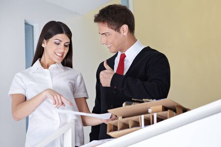 Architect near woman with blueprint holding thumbs up photo