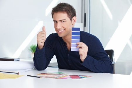 style advice: Designer with blue color samples at his desk in the office holding thumbs up
