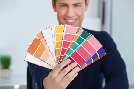 place of work: Happy graphic designer holding color fan in his hand