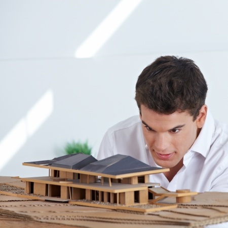 Architect in office looking at house model made of wood and cardboard photo