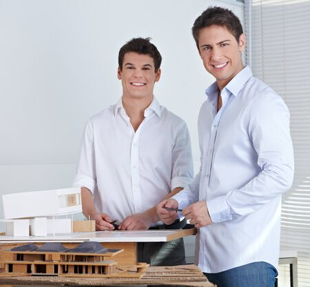 architectural studies: Two happy architects in their office with model of a modern house Stock Photo