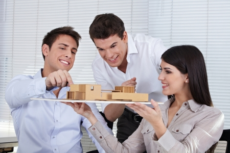 Three architects in their office discussing a building model photo