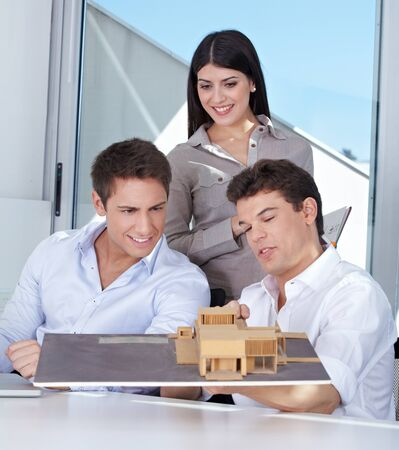 architectural firm: Team of three architects with house model in their office