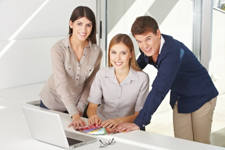 architectural firm: Group of people doing color consultation at the laptop computer in an office Stock Photo