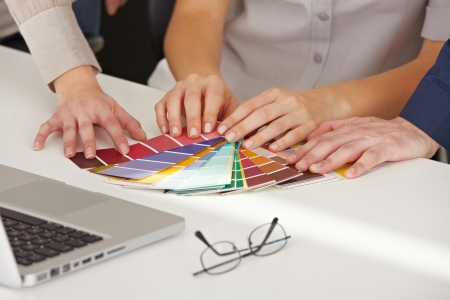 architectural firm: Many hands with different color pattern samples on the office table
