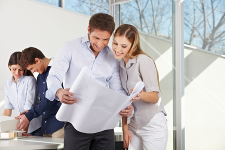 architectural firm: Happy couple looking at architectural drawing in architecture office