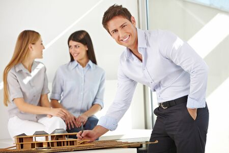 architectural studies: Happy architect in office working on a house model Stock Photo
